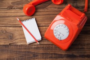 Red telephone on wooden table with notepad